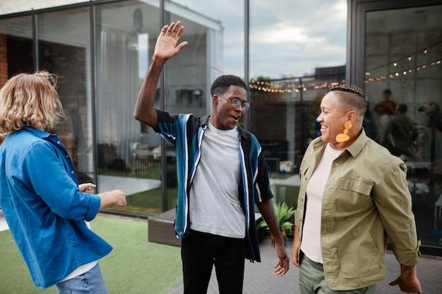 Trois jeunes s'amusant tout en profitant d'une fête en plein air sur le toit, espace de copie