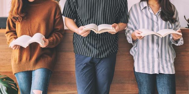 Trois jeunes se tiennent debout et aiment lire des livres ensemble