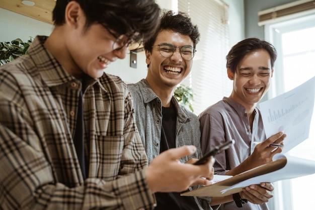 Trois jeunes travailleurs asiatiques discutant de leur produit