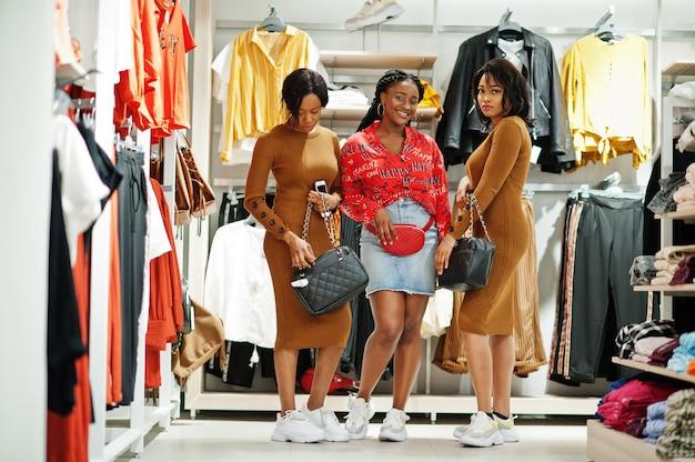 Trois jolie femme en robe tunique brune posée au magasin de vêtements avec des sacs à main.