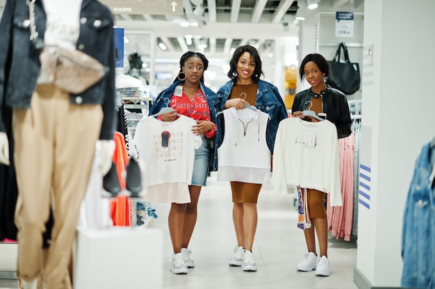 Trois jolie femme en robe tunique brune posée au magasin de vêtements