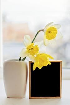 Trois jonquilles dans un vase près d'un cadre en bois vide avec cadre noir pour insérer l'image. fleurs de printemps sur le rebord de la fenêtre.