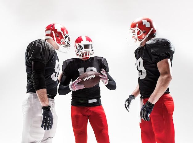 Les trois joueurs de football américain posant avec ballon