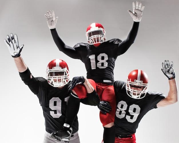 Les trois joueurs de football américain posant sur fond blanc
