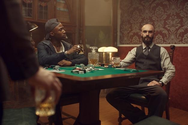 Trois joueurs de poker avec whisky et cigares assis à la table