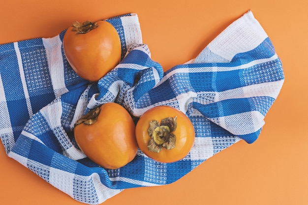 Trois kakis mûrs sur un drap bleu à carreaux