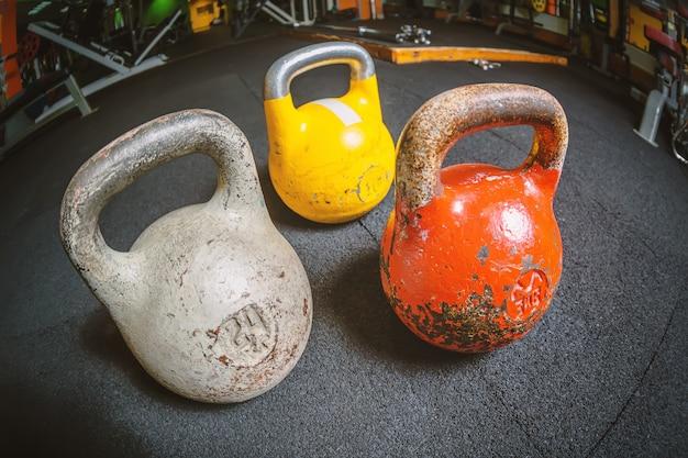 Trois kettlebell différents sur un sol dans le centre sportif de gym fitness.