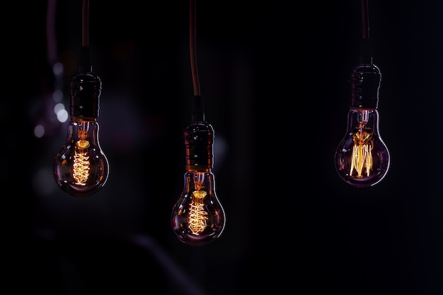 Trois lampes lumineuses sont suspendues dans l'obscurité du boke. concept de décor et d'ambiance.