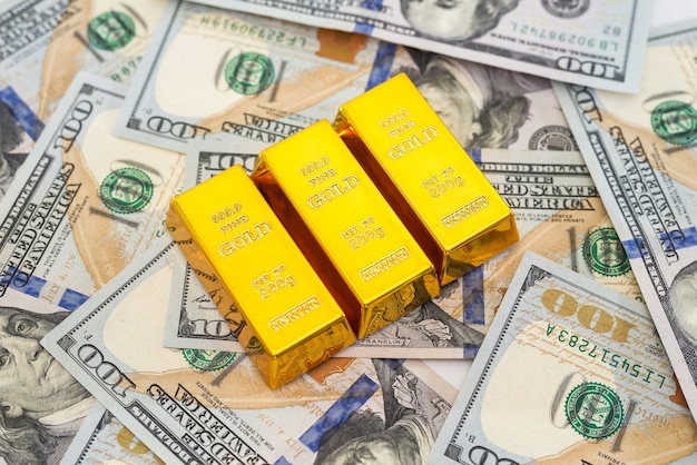 Trois lingots d'or contre des dollars américains.
