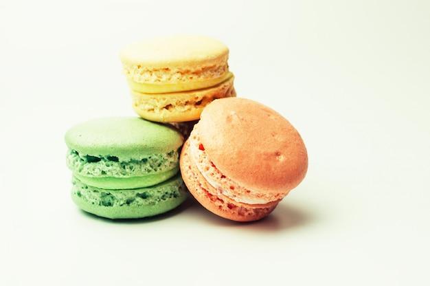 Trois macarons colorés frais se trouvent dans un tas au centre.