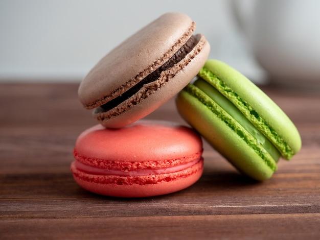 Trois macarons sur un fond en bois. le dos a un fond flou clair. vue de côté. délicieux dessert sucré