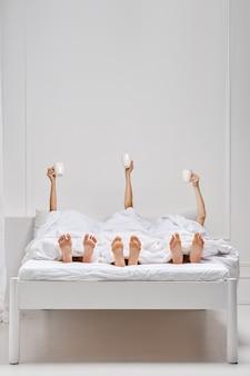 Trois mains féminines au lit tenant une tasse de café frais sur la couverture