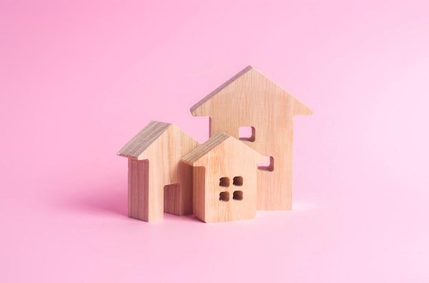 Trois maisons sur un fond rose. achat et vente de biens immobiliers, construction.