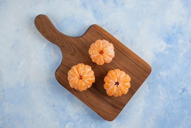 Trois mandarines fraîches pelées sur une planche à découper en bois. vue de dessus