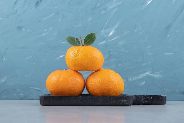 Trois mandarines fraîches sur une planche à découper noire.