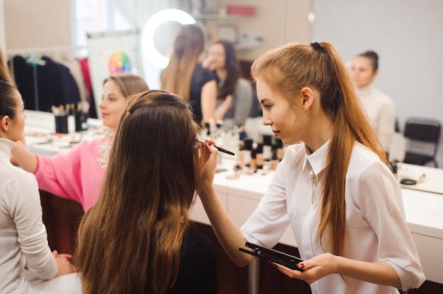 Trois maquilleurs professionnels travaillent avec de belles jeunes femmes. ecole de maquillage professionnel.