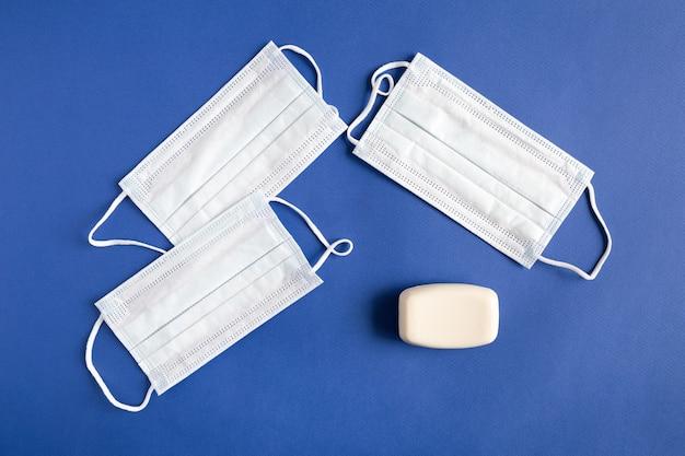 Trois masques médicaux bleus et savon à main blanc à plat sur papier
