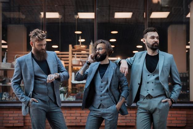 Trois mecs en costumes gris contre la devanture en brique