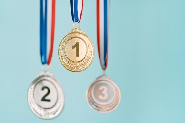Trois médailles (or, argent, bronze) sur fond bleu.concept de récompense et de victoire.espace de copie