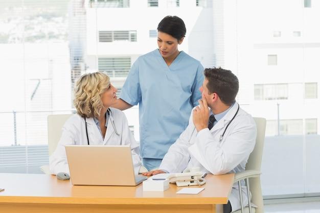 Trois médecins concentrés en discussion