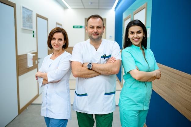 Trois médecins souriants en uniforme debout dans le couloir de la clinique. médecin spécialiste en hôpital, laryngologiste ou oto-rhino-laryngologiste, gynécologue ou mammologue, chirurgien