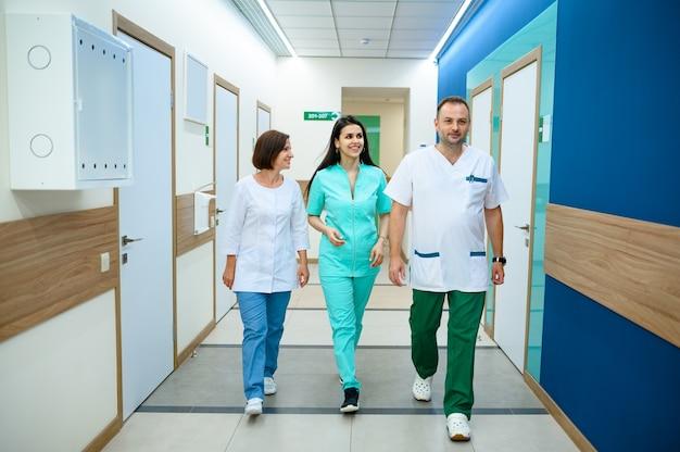 Trois médecins souriants en uniforme marchant dans le couloir de la clinique. médecin spécialiste en hôpital, laryngologiste ou oto-rhino-laryngologiste, gynécologue ou mammologue, chirurgien
