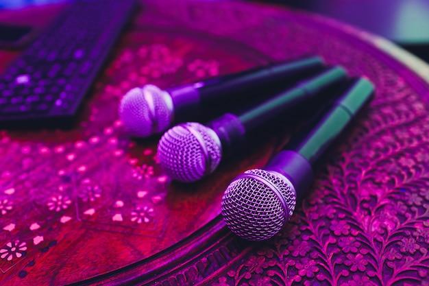 Trois microphones en groupe sur une table rouge avec espace de copie.