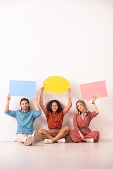 Trois milléniaux amicaux joyeux en tenue décontractée tenant de grandes bulles de papier vierge de différentes couleurs alors qu'il était assis le long du mur sur le sol