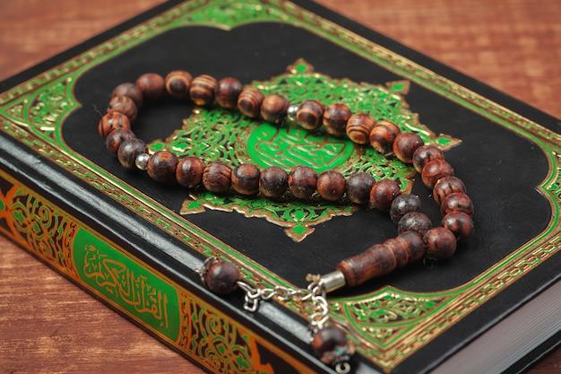 Trois mois. livre sacré islamique coran avec des perles de chapelet.