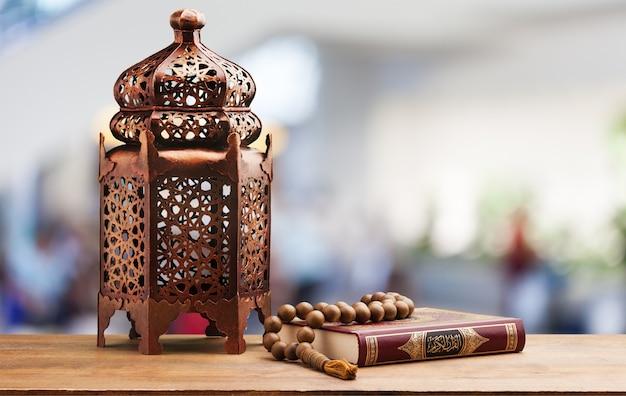 Trois mois.livre saint islamique coran avec chapelet sous une lumière douce.