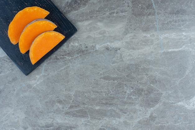 Trois morceaux de citrouille sur la planche à découper, sur la table en marbre.