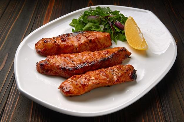 Trois morceaux de filet de saumon grillé, truite, aux herbes et citron, sur une assiette blanche, sur une table en bois