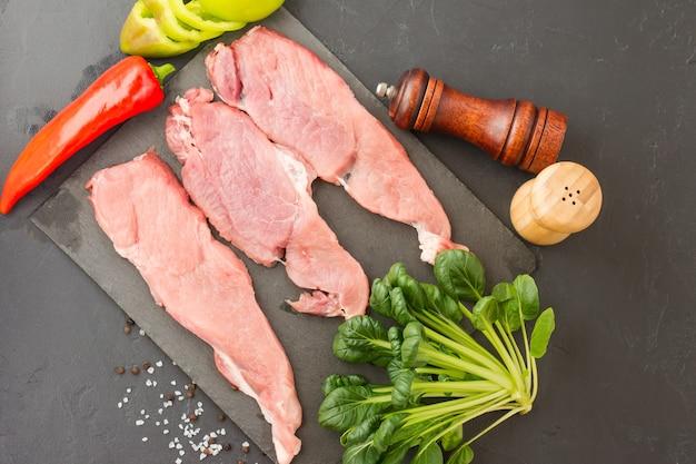 Trois morceaux de filet de viande de veau parfaits sur une ardoise avec des épices et des feuilles d'épinards.