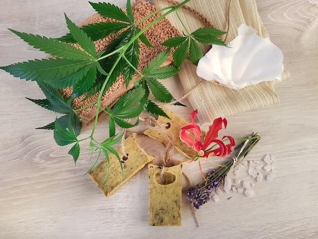 Trois morceaux de savon végétalien parfumé à base de plantes et de fleurs et ses ingrédients sur une table vintage en bois blanc. branche de chanvre, bouteille d'huile, lavande et sel. mode de vie sain.