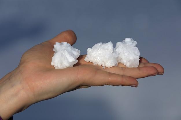 Trois morceaux de sel sur la main d'une femme dans le salar de uyuni. bolivie. amérique du sud.