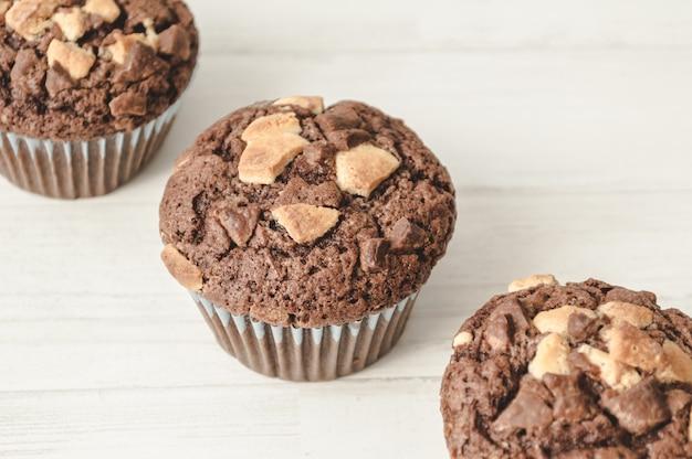 Trois muffins au chocolat alignés en diagonale sur fond blanc.