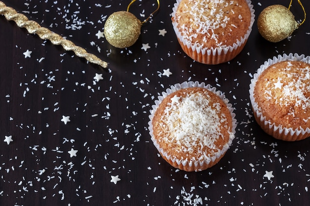 Trois muffins faits maison décorent la poudre de noix de coco sur du bois foncé