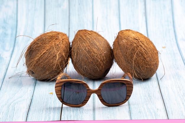 Trois noix de coco entières et verres en bois sur un fond en bois bleu