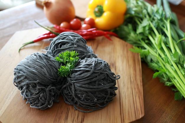 Trois nouilles au charbon noir avec céleri, oignon, piment, mini tomate sur les planches en bois