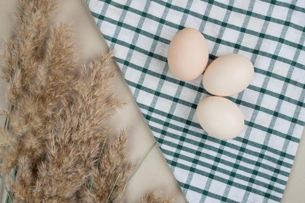 Trois œufs blancs de poulet frais sur nappe.