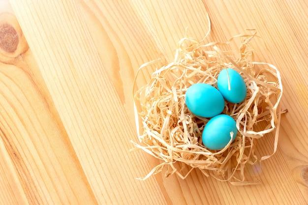 Trois oeufs bleus dans un nid sur un fond en bois clair. pâques célébrer le concept.