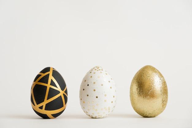 Trois oeufs décorés en or de pâques. concept de pâques minimal