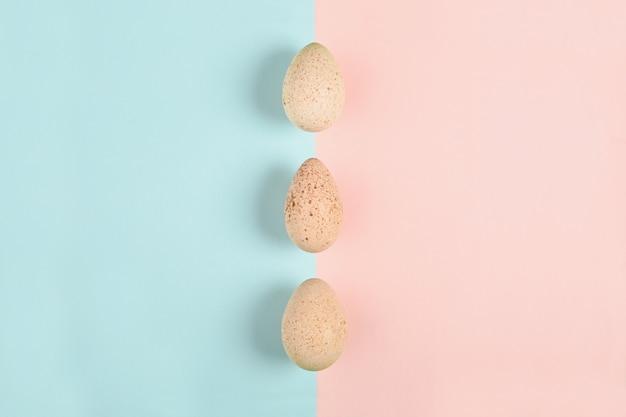 Trois oeufs de dinde sur une surface colorée. concept alimentaire dans un style minimal. vue de dessus. décoration alternative.