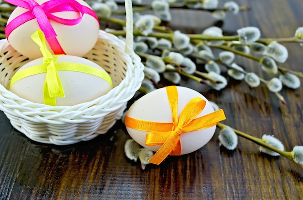 Trois oeufs de pâques attachés avec des rubans colorés, panier en osier blanc, brindilles de saule sur une planche en bois