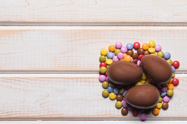 Trois oeufs de pâques au chocolat entiers sur des bonbons gemmes sur une table en bois