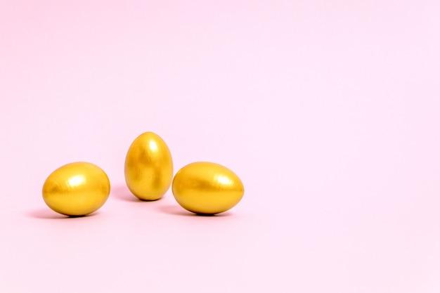 Trois oeufs de pâques décorés de peinture or sur fond rose. concept pour pâques, printemps. mise au point sélective. copiez l'espace.