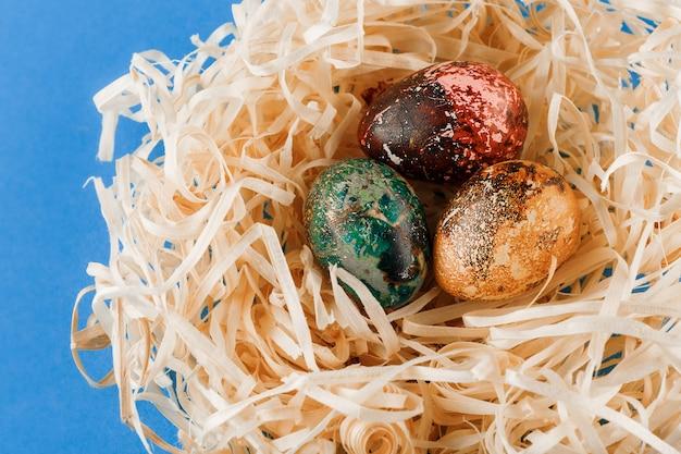 Trois œufs de pâques peints reposent dans un nid de copeaux.