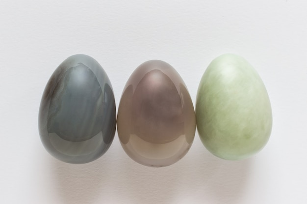 Trois oeufs de pâques en pierre précieuse décorative sur une surface blanche.
