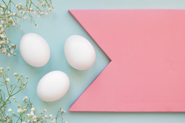 Trois œufs de poule blancs avec des fleurs avec une copie de l'espace. l'image de marque