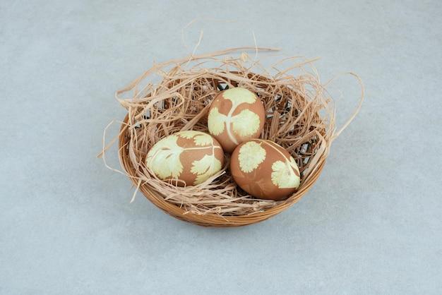 Trois œufs de poule peints dans du foin sur un panier en osier.